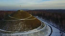 Winter flight over a forest and a mound